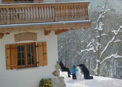 Gäste vor dem Haus beim Schneemannbauen